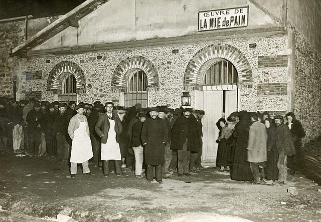 File des pauvres attendant de se restaurer à la Mie de Pain, rue Charles Fourier. Il s'agit d'une soupe populaire, fondée en 1891 par les enfants du patronage et qui, depuis cette date, continue de distribuer gratuitement, chaque soir, plusieurs centaines de repas.
